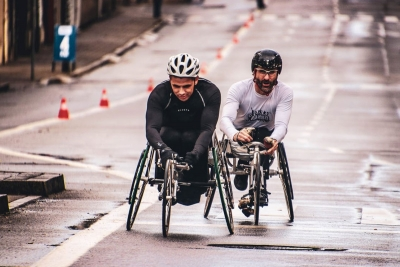 Wheelchair racers striving and competing to go up a steep hill.